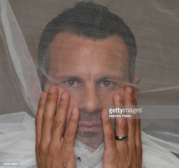 Ryan Giggs of Manchester United poses behind a malaria net at a press conference to launch a new partnership with children's charity UNICEF that will...