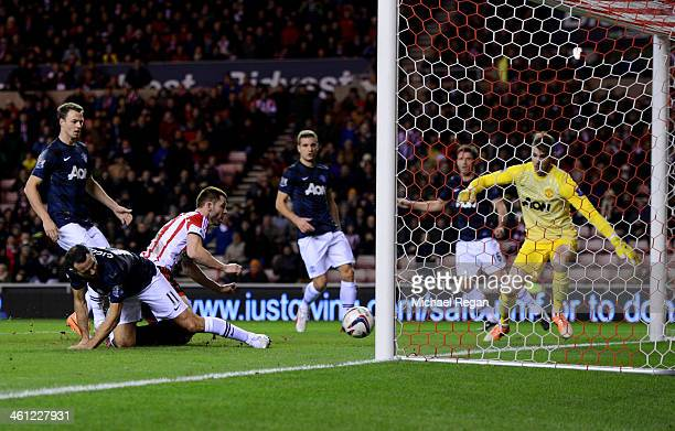 Ryan Giggs of Manchester United scores an own goal under pressure from Phil Bardsley of Sunderland for Sunderland's first goal during the Capital One...
