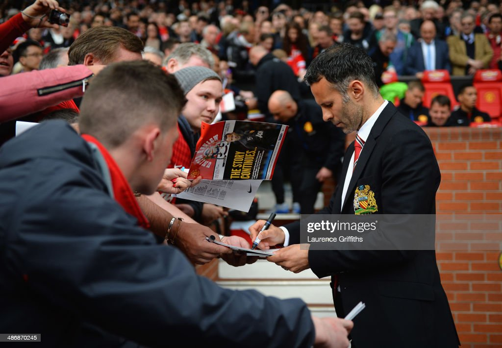 Ryan Giggs of Manchester United signs autographs during the Barclays Premier League match between Manchester United and Norwich City at Old Trafford on April 26, 2014 in Manchester, England.