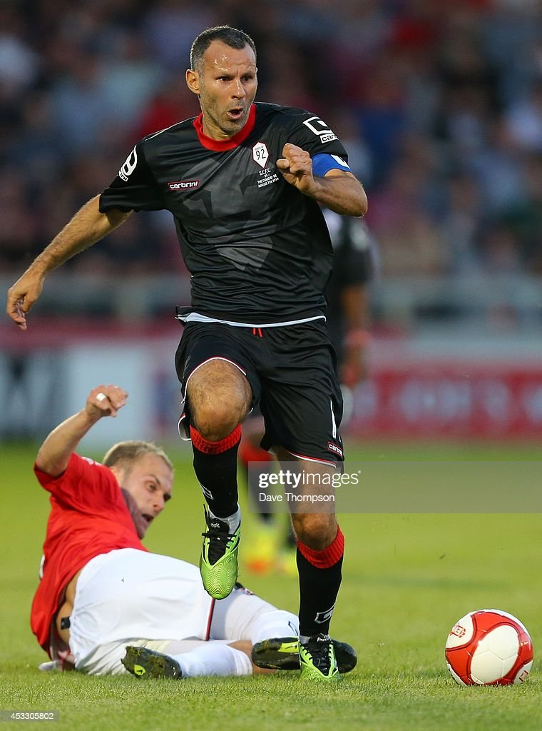 Ryan Giggs of the Class of '92 XI gets away from Nicky Platt of Salford City during the match between Salford City and the Class of '92 XI at AJ Bell Stadium on August 7, 2014 in Salford, England.