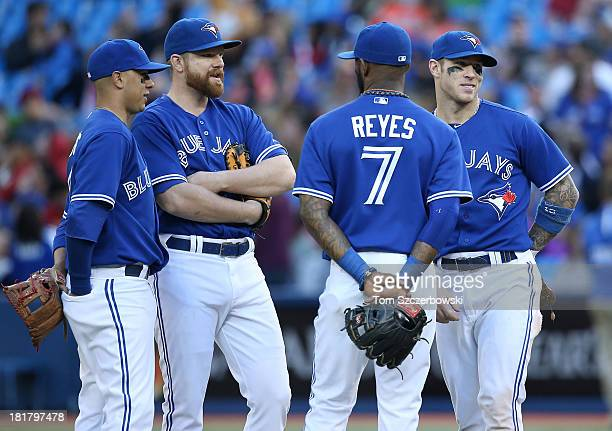 Ryan Goins and Adam Lind and Jose Reyes and Brett Lawrie of the Toronto Blue Jays talk in the infield during a pitching change in the eighth inning...