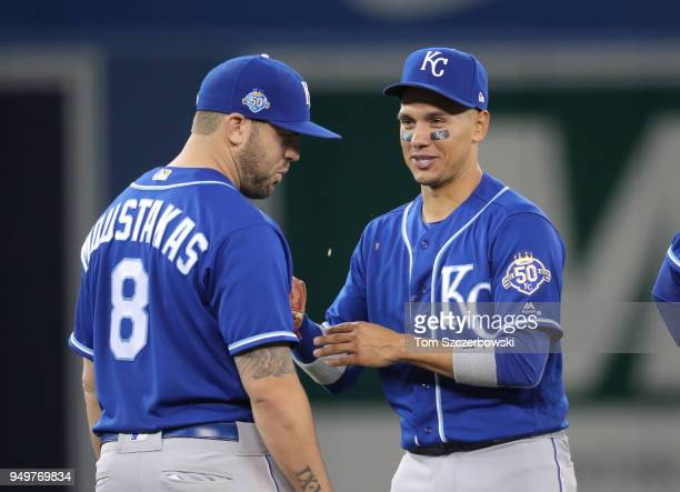 Ryan Goins of the Kansas City Royals talks to Mike Moustakas during a pitching change in the seventh inning during MLB game action against the...