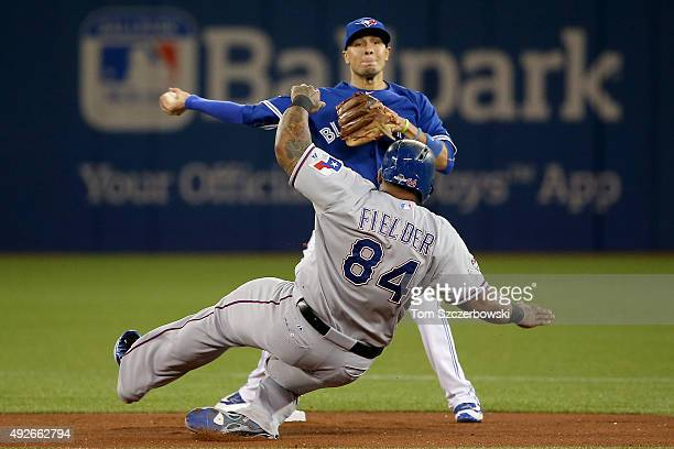 Ryan Goins of the Toronto Blue Jays attempts to turn a double play as Prince Fielder of the Texas Rangers is out at second base in the first inning...