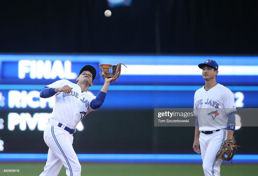 Ryan Goins #17 of the Toronto Blue Jays catches a pop up as Darwin Barney #18 watches in the third inning during MLB game action against the Tampa Bay Rays at Rogers Centre on August 16, 2017 in Toronto, Canada.