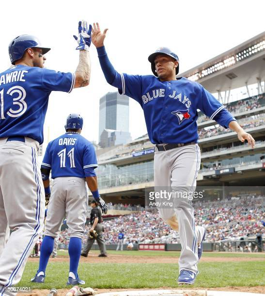 Ryan Goins of the Toronto Blue Jays celebrates Brett Lawrie after Goins scored on a hit by Blue Jays' Jose Reyes in the 8th inning against the...