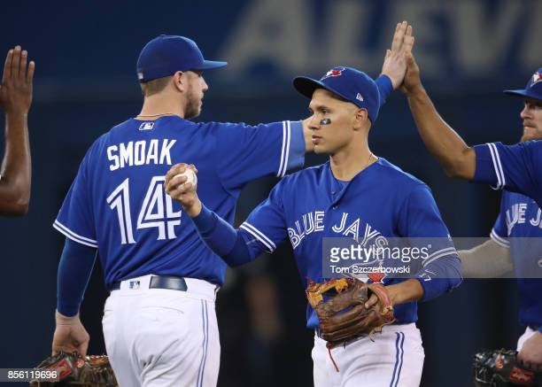 Ryan Goins of the Toronto Blue Jays celebrates their victory with Justin Smoak and teammates during MLB game action against the New York Yankees at...
