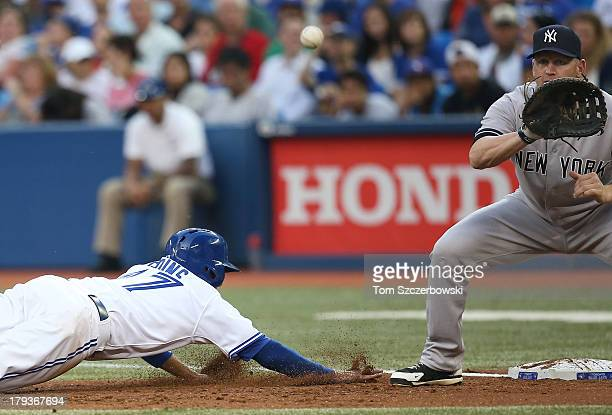 Ryan Goins of the Toronto Blue Jays dives back to first base on a pickoff throw in the first inning during MLB game action as Lyle Overbay of the New...