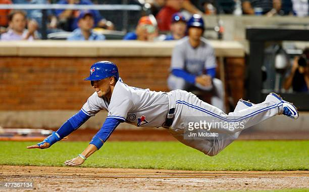 Ryan Goins of the Toronto Blue Jays dives home for an eighth inning run on a sacrifice fly against the New York Mets at Citi Field on June 16 2015 in...