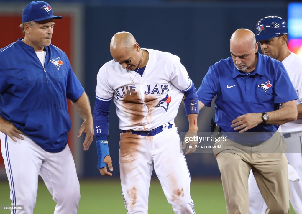 Ryan Goins #17 of the Toronto Blue Jays exits the game with his arm bleeding with the assistance of trainer George Poulis and manager John Gibbons #5 after he was stepped on by Daniel Robertson of the Tampa Bay Rays in the sixth inning during MLB game action at Rogers Centre on August 16, 2017 in Toronto, Canada.