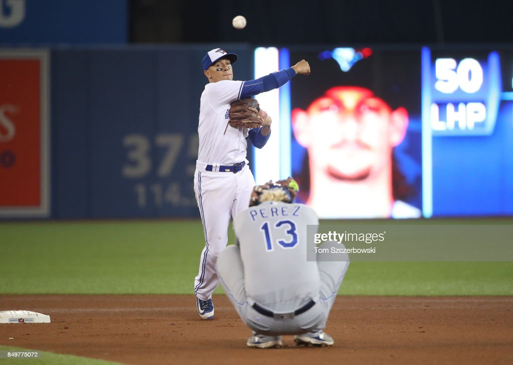 Ryan Goins #17 of the Toronto Blue Jays gets the force out of Salvador Perez #13 of the Kansas City Royals at second base but cannot turn the double play in the seventh inning during MLB game action at Rogers Centre on September 19, 2017 in Toronto, Canada.
