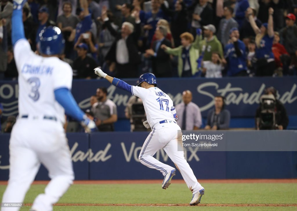 Ryan Goins #17 of the Toronto Blue Jays is celebrates as he hits a game-winning RBI single as Ezequiel Carrera #3 jogs home to score the winning run in the ninth inning during MLB game action against the Cleveland Indians at Rogers Centre on May 10, 2017 in Toronto, Canada.