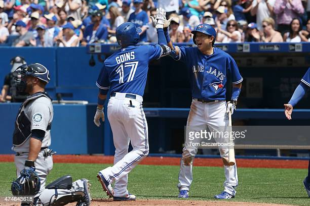 Ryan Goins of the Toronto Blue Jays is congratulated by Munenori Kawasaki after hitting a tworun home run in the fifth inning during MLB game action...