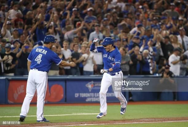 Ryan Goins of the Toronto Blue Jays is congratulated by third base coach Luis Rivera after hitting a grand slam home run in the sixth inning during...