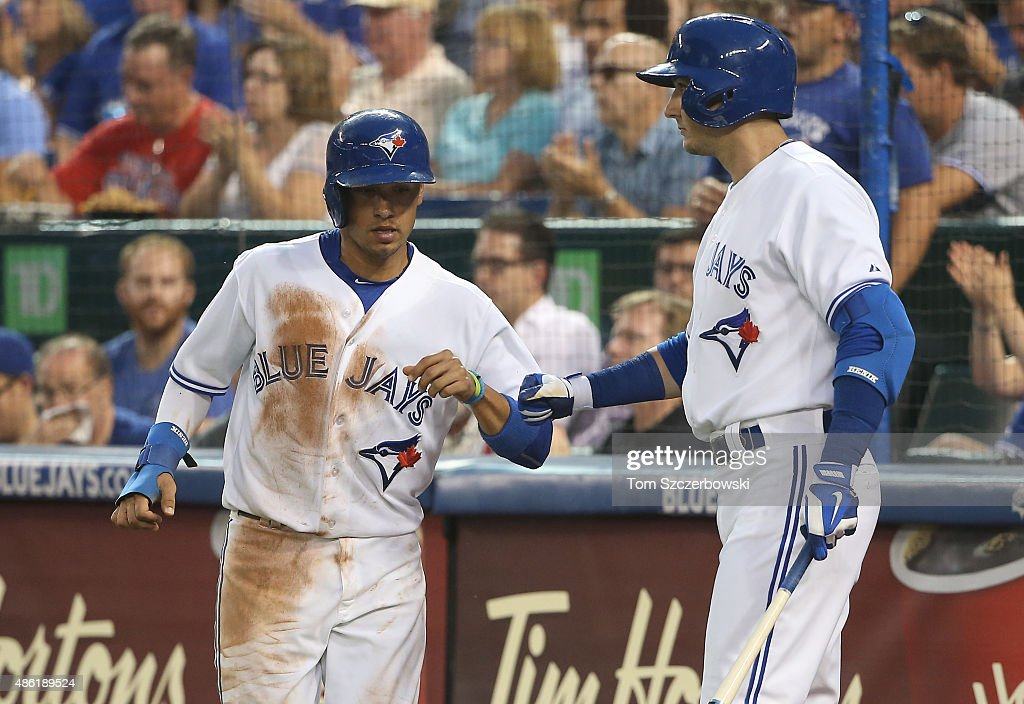 Ryan Goins #17 of the Toronto Blue Jays is congratulated by Troy Tulowitzki #2 after scoring a run on a sacrifice fly in the third inning during MLB game action against the Cleveland Indians on September 1, 2015 at Rogers Centre in Toronto, Ontario, Canada.