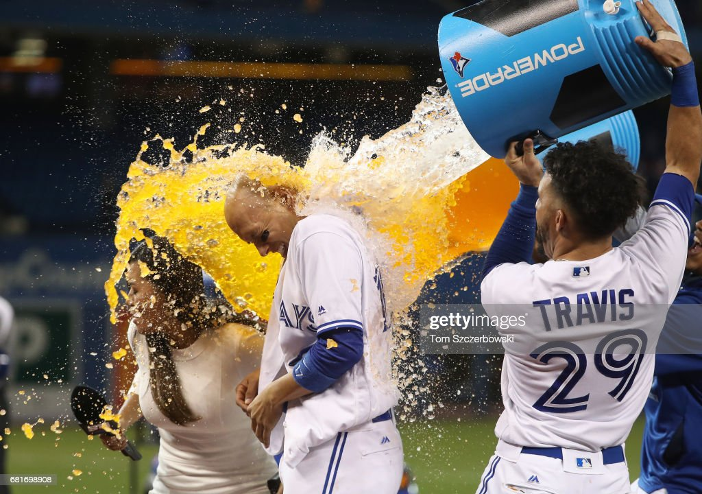 Ryan Goins #17 of the Toronto Blue Jays is doused by Devon Travis #29 after hitting a game-winning RBI single in the ninth inning during MLB game action against the Cleveland Indians at Rogers Centre on May 10, 2017 in Toronto, Canada.