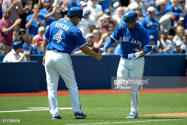 Ryan Goins of the Toronto Blue Jays shakes hands with third base coach Luis Rivera after hitting a solo home run during the game against the...