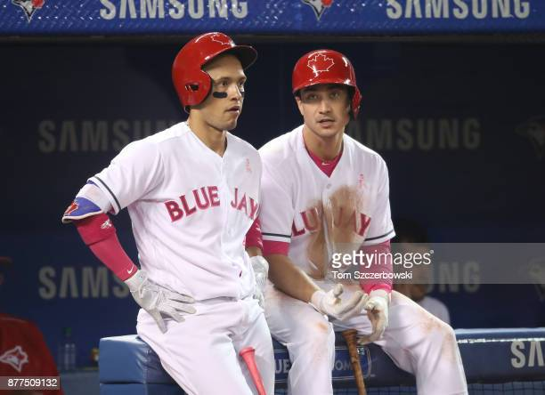 Ryan Goins of the Toronto Blue Jays talks to Darwin Barney in front of the dugout during a break in the action in the fourth inning during MLB game...