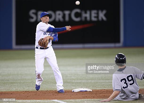 Ryan Goins of the Toronto Blue Jays turns a double play in the fourth inning during MLB game action as Mark Reynolds of the New York Yankees slides...