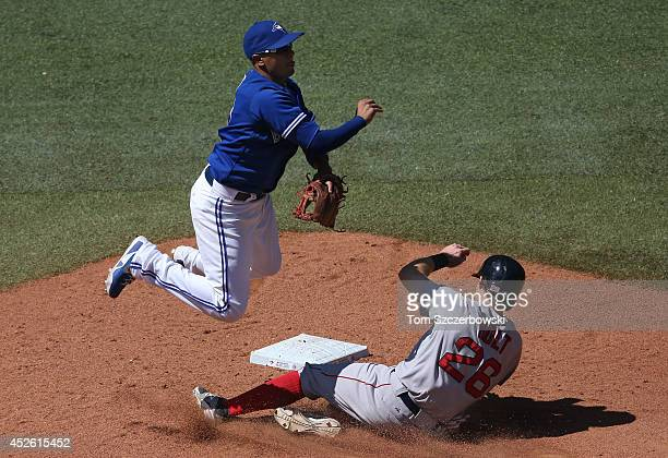 Ryan Goins of the Toronto Blue Jays turns a double play in the ninth inning during MLB game action as Brock Holt of the Boston Red Sox slides into...
