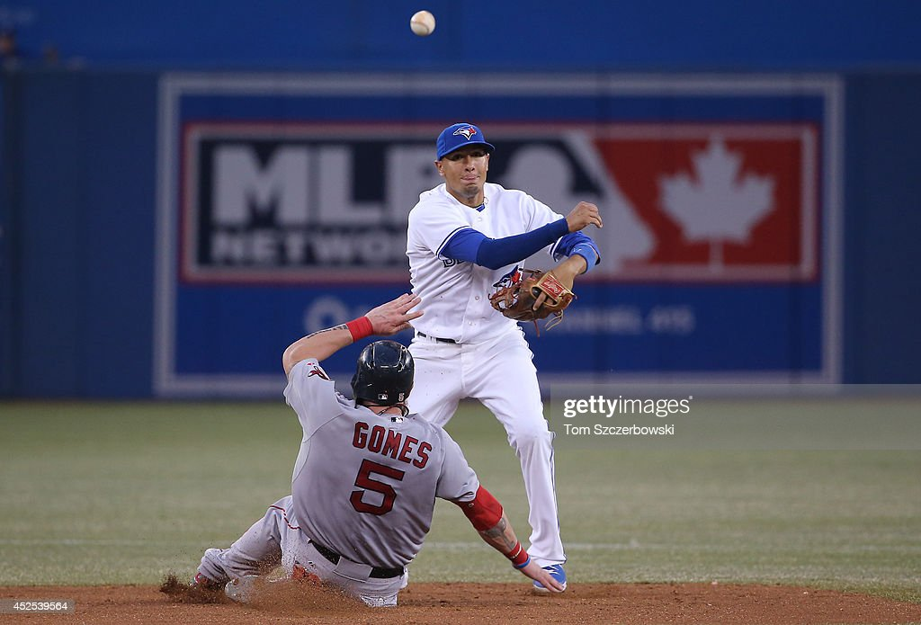 Ryan Goins #48 of the Toronto Blue Jays turns a double play in the sixth inning during MLB game action as Jonny Gomes #5 of the Boston Red Sox slides into second base on July 22, 2014 at Rogers Centre in Toronto, Ontario, Canada.