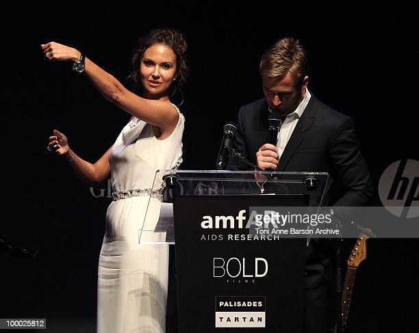 Ryan Gosling speaks as Svetlana Metkina holds up a watch for auction during amfAR's Cinema Against AIDS 2010 benefit gala at the Hotel du Cap on May...