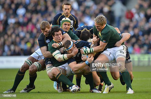 Ryan Grant Scotland is tackled by Francois Louw and Jean de Villiers of South Africa during the international match between Scotland and South Africa...