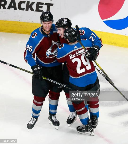 Ryan Graves of the Colorado Avalanche celebrates his third period goal against the St. Louis Blues and is joined by Mikko Rantanen and Nathan...