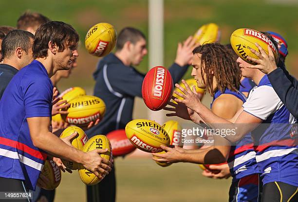 Ryan Griffen and Luke Dahlhaus of the Bulldogs pass the ball during a Western Bulldogs AFL training session at Whitten Oval on July 31 2012 in...