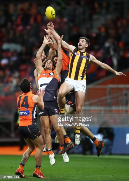 Ryan Griffen of the Giants is challenged by Ricky Henderson of the Hawks during the round 15 AFL match between the Greater Western Sydney Giants and...