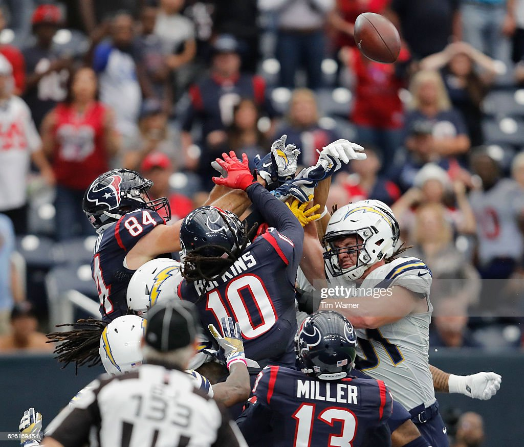 Ryan Griffin #84 of the Houston Texans and DeAndre Hopkins #10 of the Houston Texans battle with Kyle Emanuel #51 of the San Diego Chargers for a pass in the endzone during the fourth quarter of the game at NRG Stadium on November 27, 2016 in Houston, Texas.
