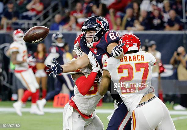 Ryan Griffin of the Houston Texans drops the ball as he is pressured by Tyvon Branch and Husain Abdullah of the Kansas City Chiefs during the fourth...