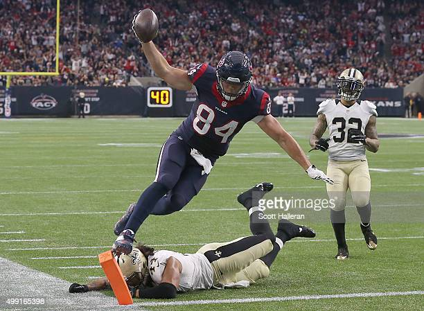 Ryan Griffin of the Houston Texans jumps and lands on the pylon to score a touchdown while Vinnie Sunseri of the New Orleans Saints defends on the...