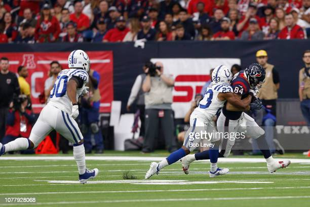 Ryan Griffin of the Houston Texans runs the ball after a catch tackled by Kenny Moore of the Indianapolis Colts in the first quarter during the Wild...