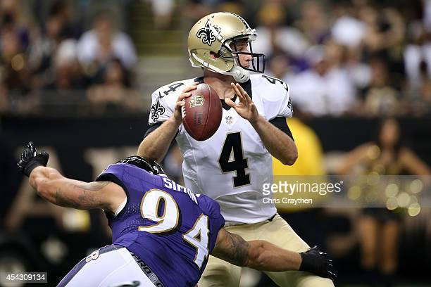 Ryan Griffin of the New Orleans Saints throws a pass under pressure from John Simon of the Baltimore Ravens in their pre season game at the...