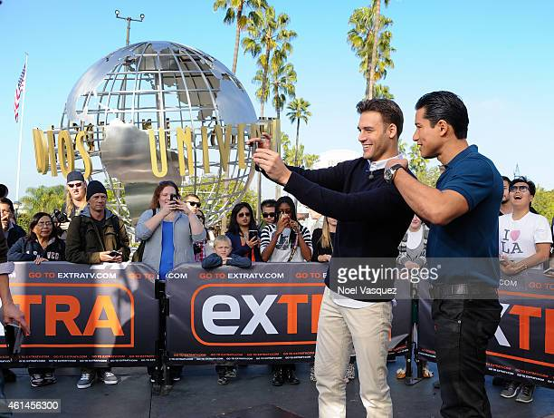 """Ryan Guzman and Mario Lopez take a selfie at """"Extra"""" at Universal Studios Hollywood on January 12, 2015 in Universal City, California."""