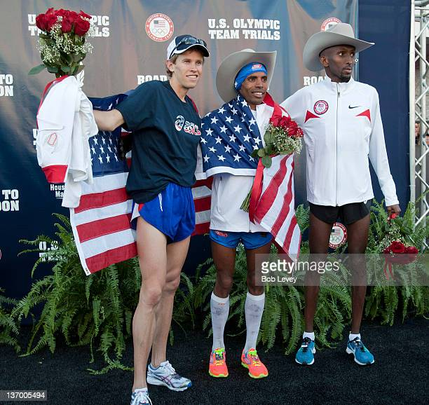 Ryan Hall Meb Keflezighi and Abdi Abdirahman pose with their cowboy hats on the stage after qualifying for the US Marathon Olympic Trials on January...