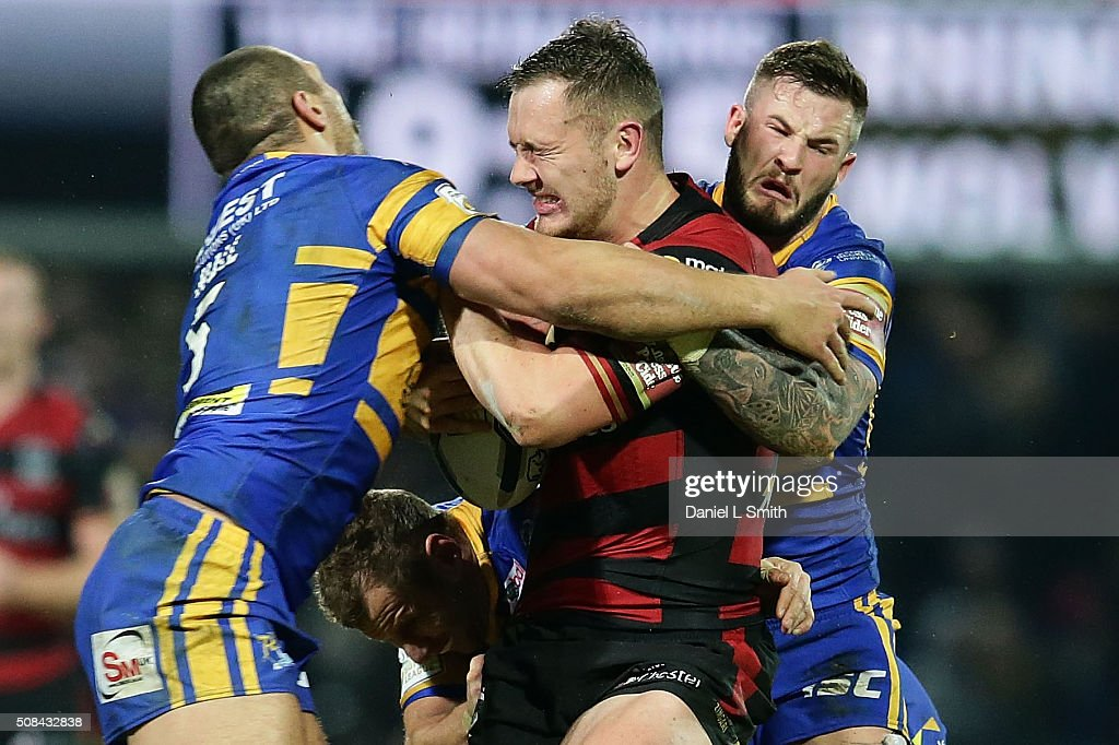 Ryan Hall of Leeds Rhinos assists Zak Hardaker of Leeds Rhinos in tackling Ben Currie of Warrington Wolves during the First Utility Super League opening match between Leeds Rhinos and Warrington Wolves at Headingley Carnegie Stadium on February 4, 2016 in Leeds, England.