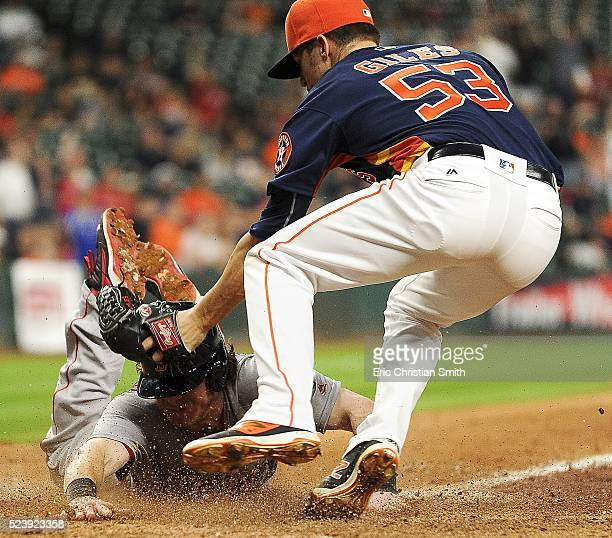 Ryan Hanigan of the Boston Red Sox beats the tag at home plate of Ken Giles of the Houston Astros after Giles' wild pitch during the twelfth inning...