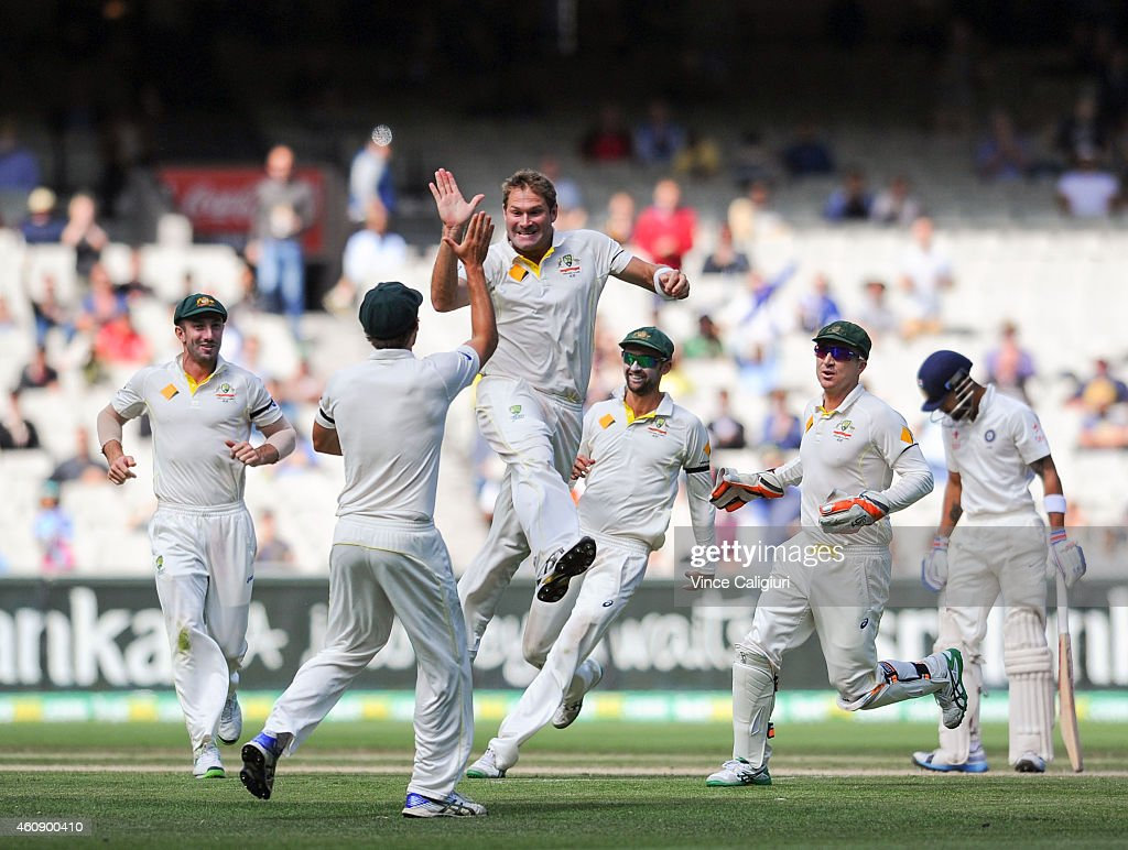 Ryan Harris of Australia celebrates with Joe Burns after dismissing Virat Kohl during day five of the Third Test match between Australia and India at Melbourne Cricket Ground on December 30, 2014 in Melbourne, Australia.
