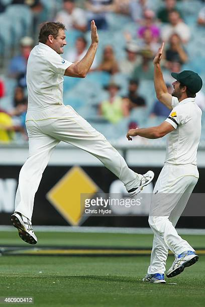 Ryan Harris of Australia celebrates with Joe Burns after taking a catch to dismiss Virat Kohli of India off the bowling of Harris during day five of...
