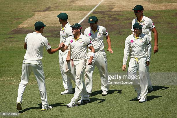 Ryan Harris of Australia is congratulated by team mates after dismissing Umesh Yadav of India during day four of the Fourth Test match between...