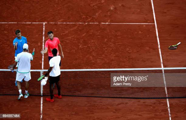 Ryan Harrison of The United States and partner Michael Venus of New Zealand shake hands with their opponants following victory in the mens doubles...