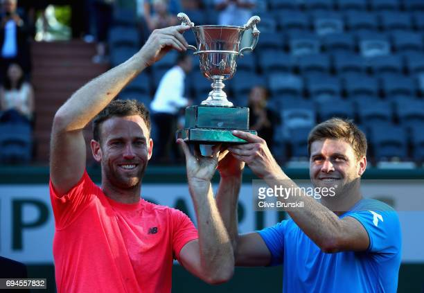 Ryan Harrison of The United States and partner Michael Venus of New Zealand celebrate victory with the trophy in the mens doubles final match against...