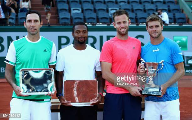 Ryan Harrison of The United States and partner Michael Venus of New Zealand hold their winners trophy as Donald Young of The United States and...