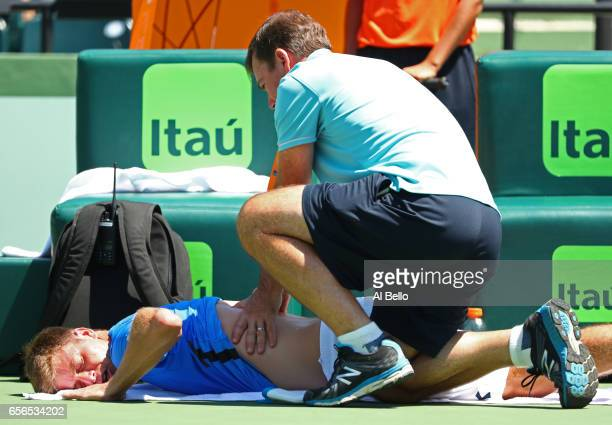 Ryan Harrison receives treatment on his back during his match against Fabio Fognini of Italy during day 3 of the Miami Open at Crandon Park Tennis...