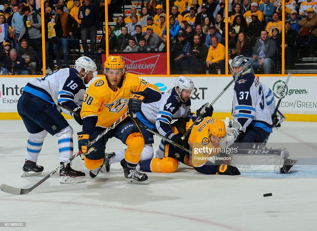 Ryan Hartman #38 and Calle Jarnkrok #19 of the Nashville Predators fight against Bryan Little #18 and Josh Morrissey #44 of the Winnipeg Jets in front of goalie Connor Hellebuyck #37 during the first period at Bridgestone Arena on March 13, 2018 in Nashville, Tennessee.