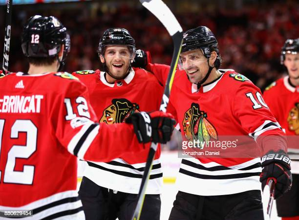 Ryan Hartman and Patrick Sharp of the Chicago Blackhawks skate in to congratulate Alex DeBrincat after DeBrincat scored his second goal of the game...