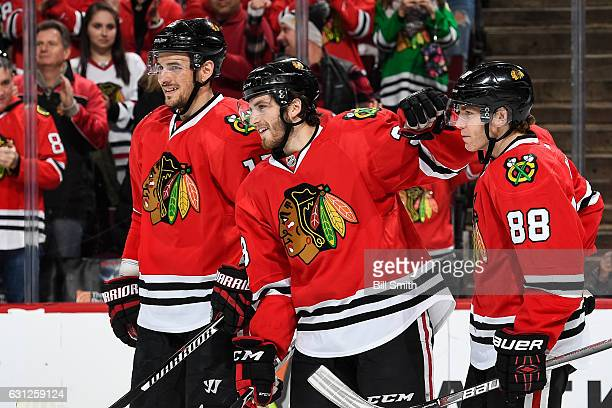 Ryan Hartman of the Chicago Blackhawks celebrates with Artem Anisimov and Patrick Kane after scoring a hat trick against the Nashville Predators in...