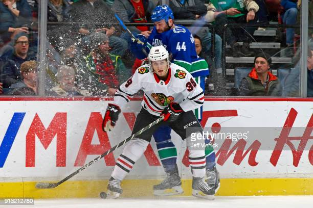 Ryan Hartman of the Chicago Blackhawks checks Erik Gudbranson of the Vancouver Canucks during their NHL game at Rogers Arena February 2 2018 in...