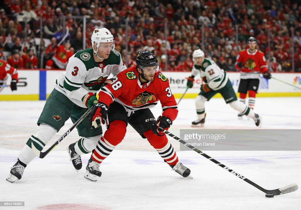 Ryan Hartman #38 of the Chicago Blackhawks controls the puck under pressure from Charlie Coyle #3 of the Minnesota Wild at the United Center on December 17, 2017 in Chicago, Illinois. The Blackhawks defeated the Wild 4-1.